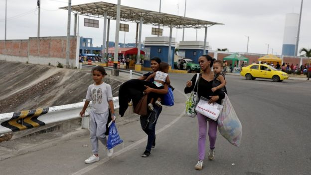 Venezuelans walk together with their children after entering Peru
