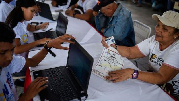 Imagem mostra pessoas se registrando para tirar o chamado carnê d pátria, uma nova identidade que o governo venezuelano criou em 2017