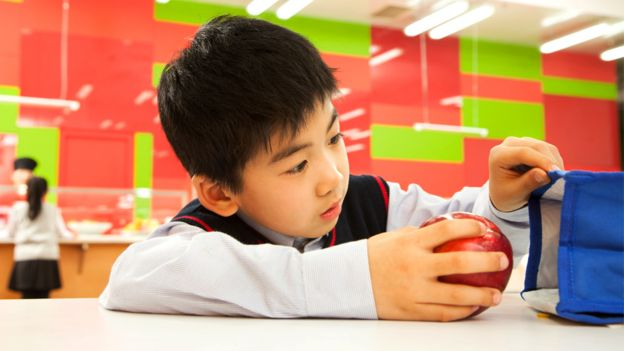 A Chinese student opens a lunch bag at a school cafeteria