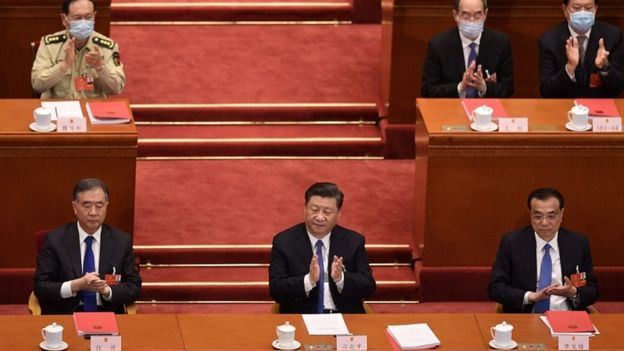 China's President Xi Jinping (c) applauds after the vote during the closing session of the National People's Congress at the Great Hall of the People in Beijing on May 28, 2020