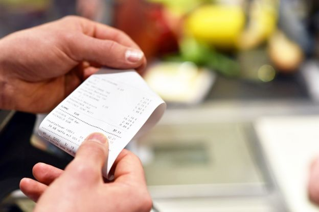 Photo of a woman looking at a receipt
