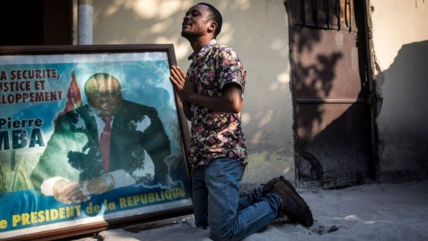A supporter of Jean-Pierre Bemba prays as he kneels next to his picture at the Congolese Liberation Movement (MLC) headquarter in Kinshasa on June 8, 2018