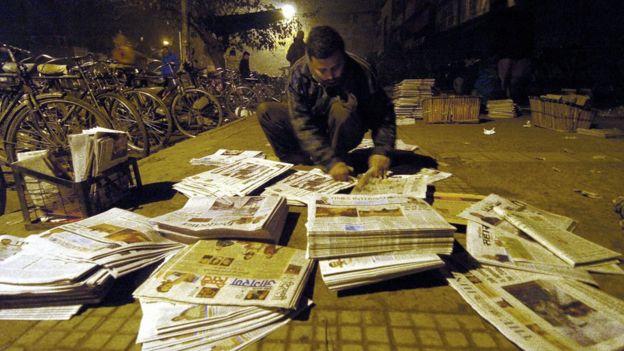 A newspaper vendor arranging stacks of newspapers