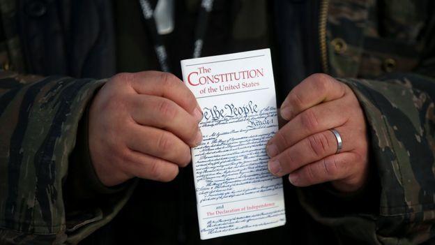 Hombre sosteniendo la Constitución de EE.UU.