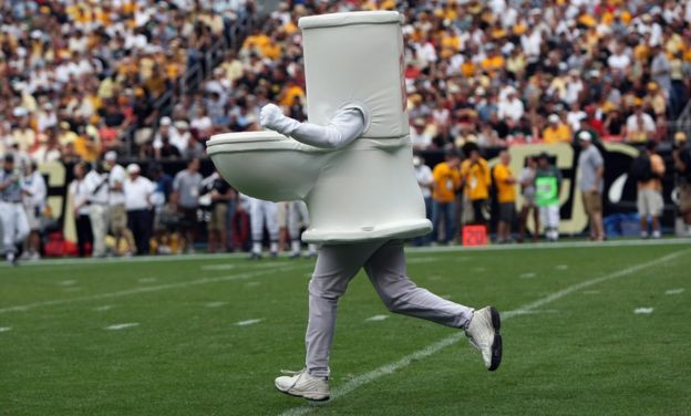 A man dressed as a toilet runs onto the field during an American football game in Denver, Colorado