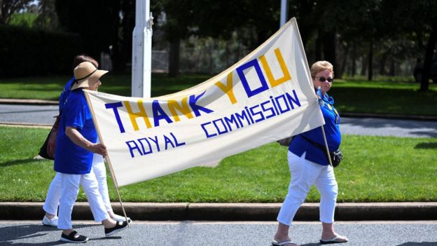 Women hold a banner thanking the Royal Commission into institutional child sexual abuse