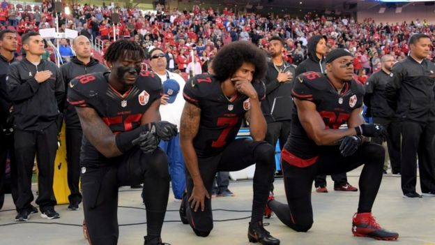 Eli Harold, Colin Kaepernick and Eric Reid (35) kneel in protest during the playing of the national anthem before a NFL game