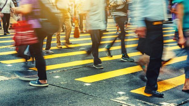 Dezenas de pessoas caminham pela rua