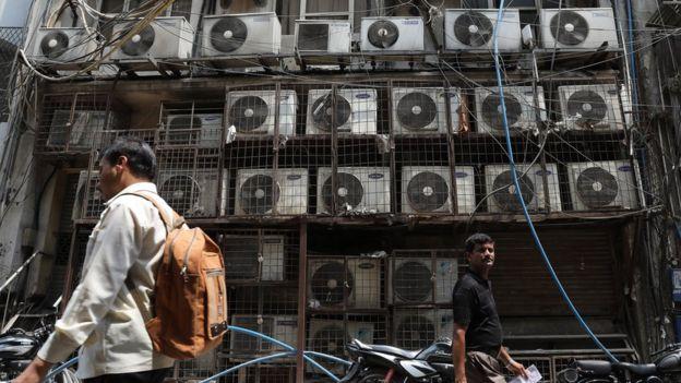 Parede coberta de aparelhos de ar-condicionado do lado de fora de um escritório, em Nova Déli.