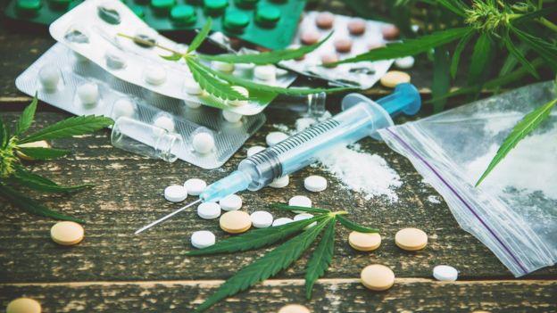 Mesa com remédios, injeção, folhas de maconha e pó