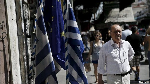 A man makes his way next to Greek national flags and a European Union flag in central Athens