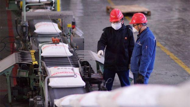Dois trabalhadores conversam ao lado de esteira de produção com tecidos