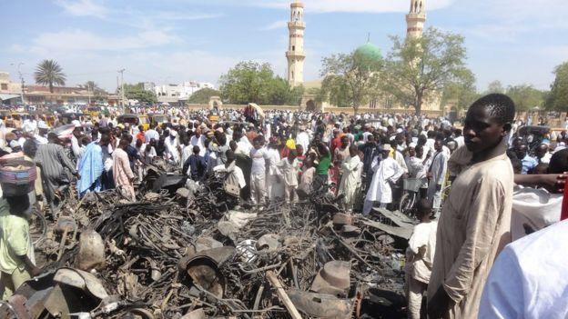 Decenas de personas observan una motocicleta quemada frente a la mezquita central de Kano, en el norte de Nigeria, el 29 de noviembre de 2014, después de un ataque suicid durante los rezos del viernes.