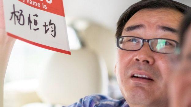 Yang Hengjun, seen in 2014 holds up a name placard
