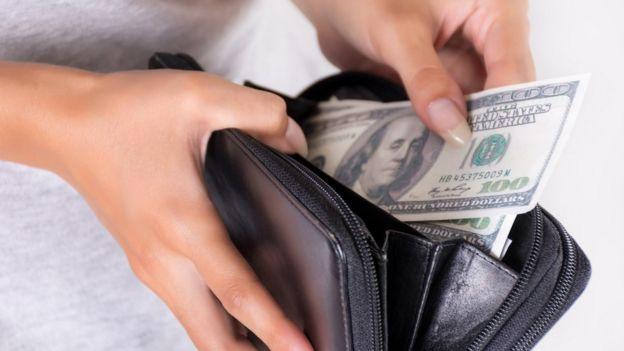 Mujer con dólares en la mano.