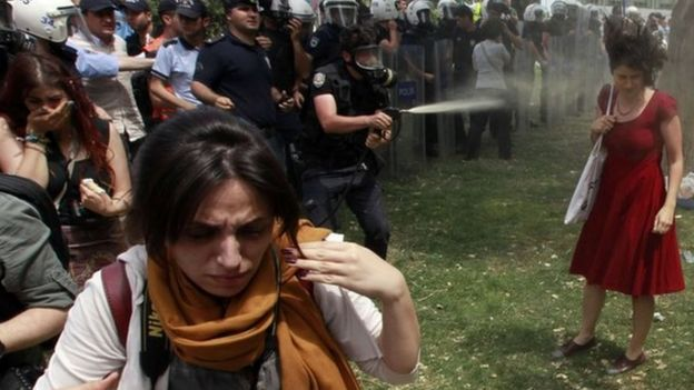 A Turkish riot policeman uses tear gas against Ceyda Sungur (in red dress, right) in Istanbul's Taksim Square in June 2013