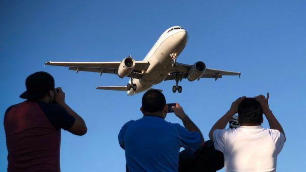 Homens olhando avião