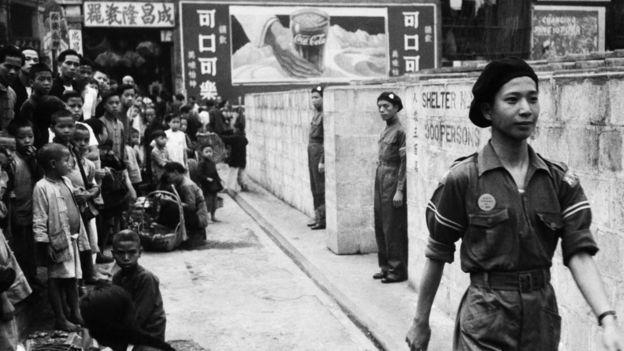 香港街頭某防空洞前小孩圍觀駐守洞口的義勇軍士兵(1941年)