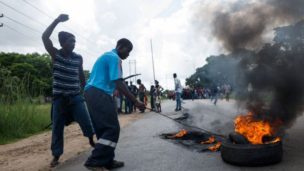 A man sets tyre on fire as angry protesters barricade the main route to Zimbabwe's capital Harare from Epworth township - January 2019