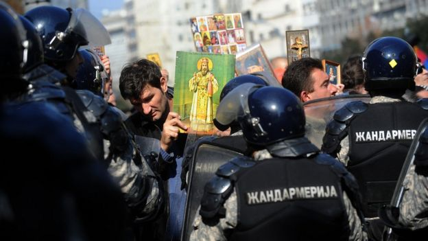An anti-gay Serb protester holds an Orthodox icon in front of riot police in the centre of Belgrade during the country's second ever Gay Pride march on 10 October 2010