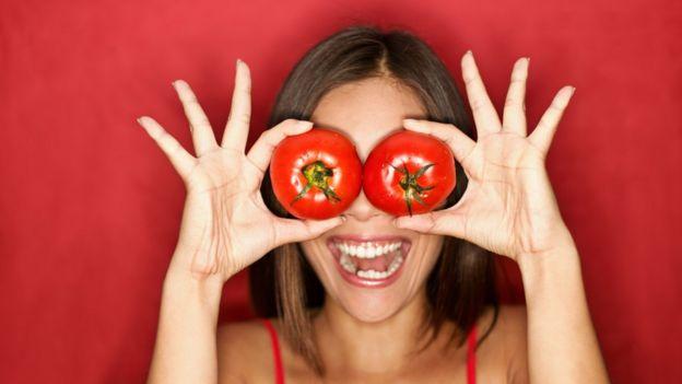 Mulher posando com tomates no rosto