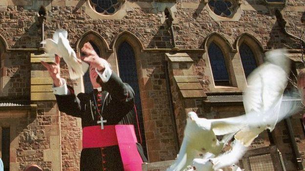El arzobispo de Adelaide, Philip Wilson, suelta unas palomas frente a la catedral de la ciudad, en 2002