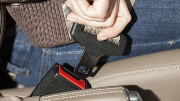 Woman doing up seat belt