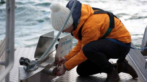 Clare Ostle manipula, do chão do barco, a máquina CPR