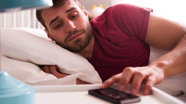 Homem mexe em despertador no celular