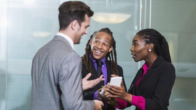 Tres personas hablando en una oficina.