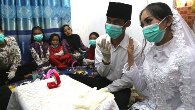 Couple wearing protective masks gets married.