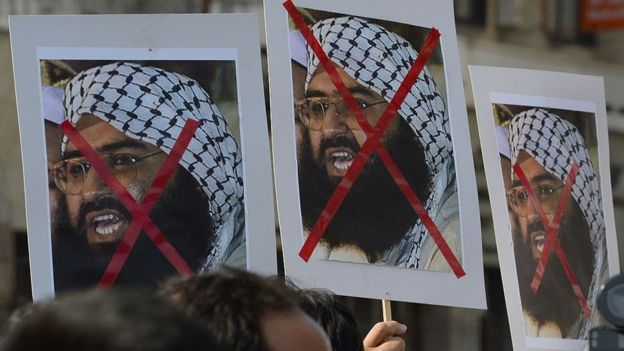 People protest carrying placards of Maulan Masood Azhar