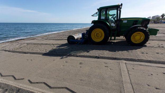 Un tractor demarca las áreas en la playa para los bañistas