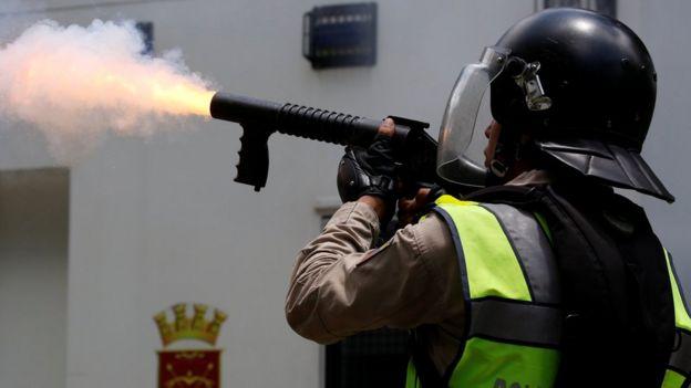 Policía disparando un cartucho de gas lacrimógeno.