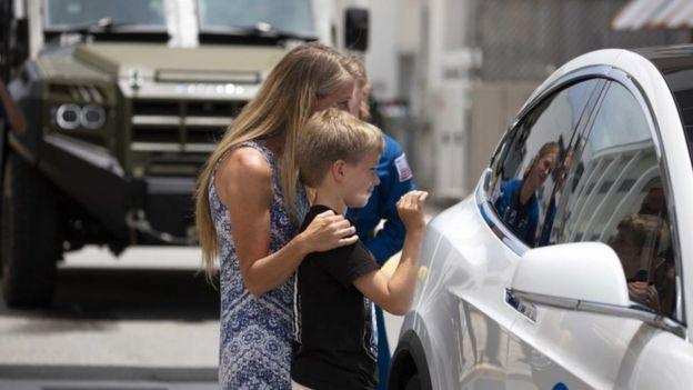 Karen Nyberg y su hijo se despiden de Doug Hurley, que va en un auto Tesla a la plataforma de lanzamiento.