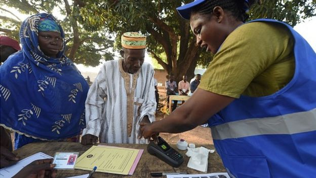 An official of the Electoral Commission (EC) helps a voter to do biometric verification before casting his vote for the presidential election at Bole district in northern Ghana, on December 7, 2016.