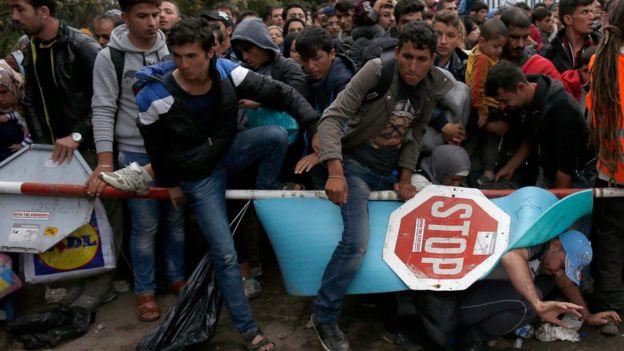 Migrants climb over barrier at Serbia-Croatia border on 19 October 2015