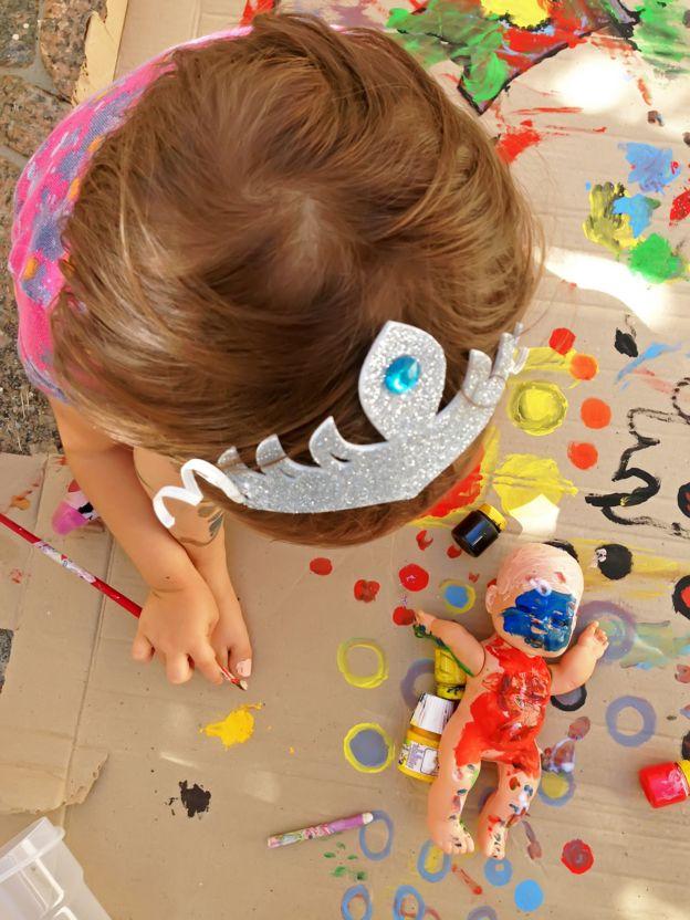 Menina com pincel na mão e boneca no chão com o corpo pintado com tintas coloridas