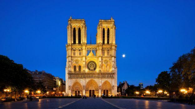 Visão frontal da catedral, que aparece iluminada em início de noite