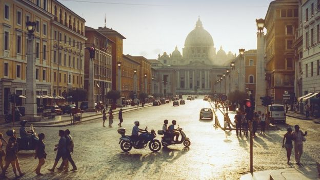 General view of the Vatican at sunset, with people and motorbikes in the foreground