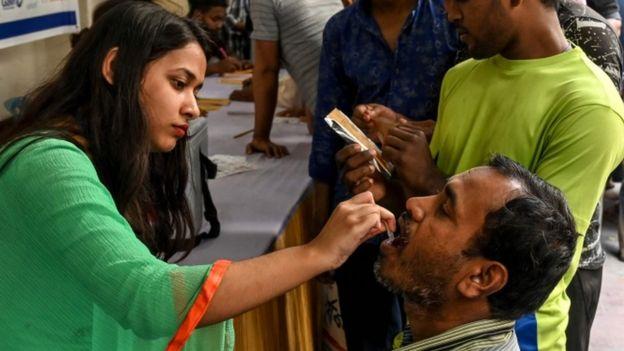 Un hombre recibe una vacuna por v�a oral de una trabajadora de la salud en Daca, Bangladesh, febrero 2020