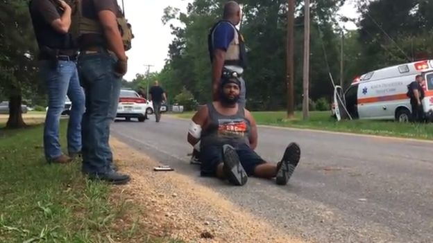 Suspect Cory Godbolt handcuffed, and sat on the ground, after being detained by police