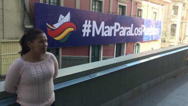 Mujer al lado de valla que dice #MarParaLosPueblos