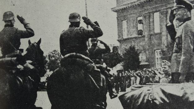 Photograph of Arthur Greiser (1897-1946), a Nazi German politician, SS-Obergruppenführer and Reichsstatthalter, saluting his troops after the Battle of Lódz, Poland. Dated 1939