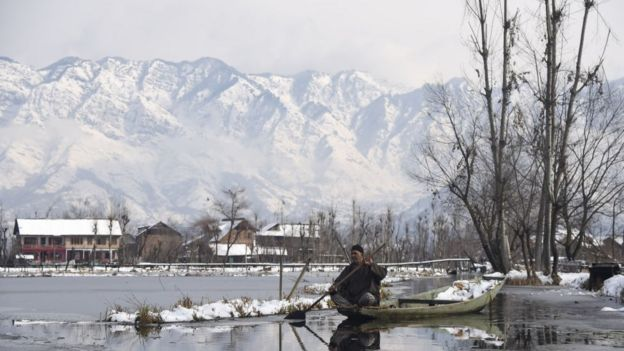 A Kashmiri boatman rows his boat on Dal Lake after fresh snowfall in Srinagar.