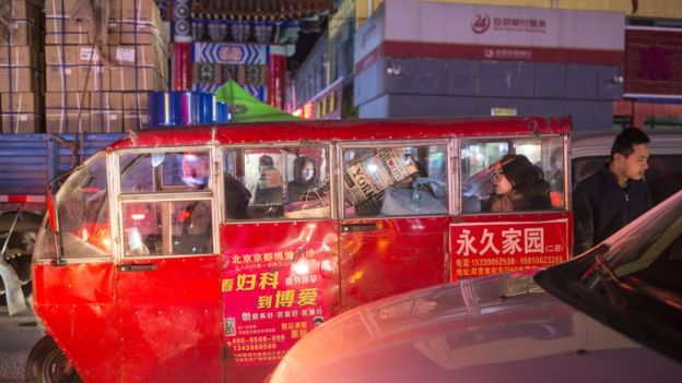 11月24日,北京通州,一位女士坐在一輛塞滿行李的三輪車裏。