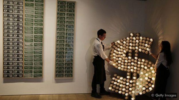 Símbolo do dólar feito de lâmpadas e refletores, criação dos artistas Tim Noble e Sue Webster, ao lado de quadros de Andy Warhol