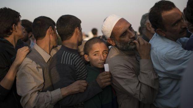 Fila de homens em campo de refugiados