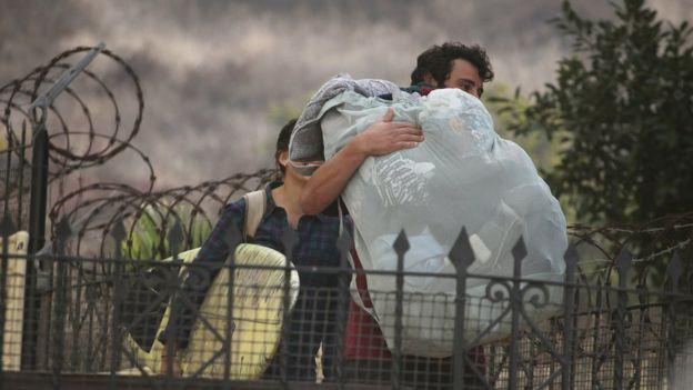 Una pareja abandona su hogar por la cercanía de un incendio en Ensenada, México