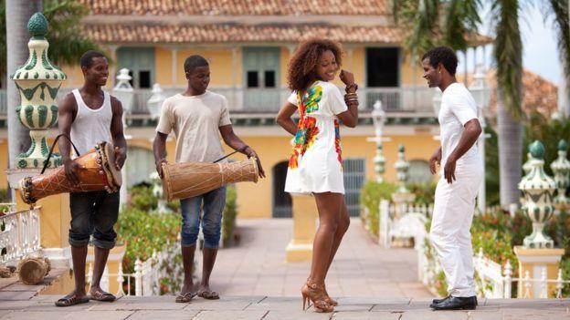 Dos personas bailando salsa y dos tocando instrumentos.